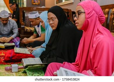 Labuan,Malaysia-May 21,2020:Malaysian muslim woman with hijab,reading the holy book Quran to celebrate the holy Ramadan Kareem feasting month in Labuan,Malaysia.