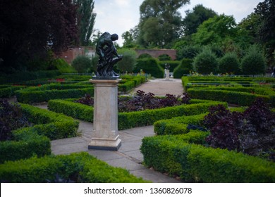 The labyrinth from flower beds with a statue of a man in the center in the park.