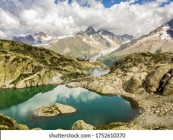 Lac Blanc and Refuge du Lac Blanc, France. Reflection of Monte Bianco range in lake, cloudy blue sky. Panoramic View Of Aiguille du Tour. Tour du Mont Blanc. Tourists trekking in French Alps, Europe