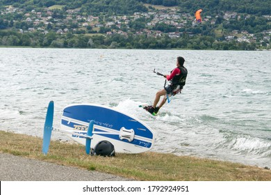 Lac Bourget, Savoie/France 17th July 2020. Wind boarding and sailboarding on an overcast day. The wind board is in the foreground with a man wind boarding in the background. Main subject is the board