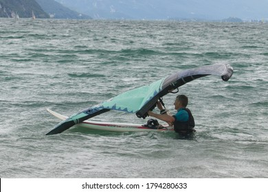 Lac Bourget, Savoie/France 17th July 2020. Wind boarding and sailboarding on an overcast day. Man with kite stood in the lake trying to keep his board and kite together