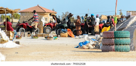LAC ROSE, SENEGAL - APR 26, 2017: Unidentified Senegalese man rides a quad bike on the salty coast of the Lake Retba, UNESCO World Heritage Site