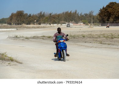 LAC ROSE, SENEGAL - APR 26, 2017: Unidentified Senegalese man rides a motorcycle on the salty coast of the Lake Retba, UNESCO World Heritage Site