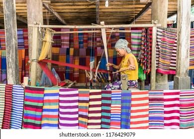 Lac Village, Mai Chau valley, Vietnam - October 18, 2016. Local woman diligently working at a loom, weaving colourful brocade fabric. Traditional patterns and colors.