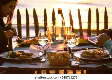 LACANAU BEACH, FRANCE- April 1, 2015 : Selective Focus on food and glasses on dinning table at seafood restaurant during summer sunset, vintage style