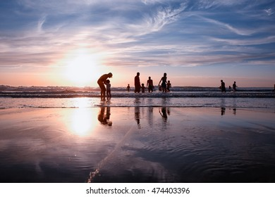 LACANAU, FRANCE - August 25, 2016: Silhouette of people playing in the water at sunset, with vintage style