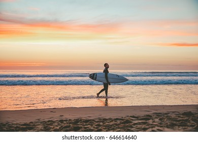 LACANAU, FRANCE - August 25, 2016: Silhouette of a surfer walking on a beach at sunset