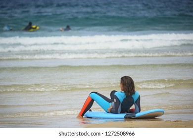 Lacanau-Ocean, France - August 2018: a woman sitting on her surf in a very relaxed position
