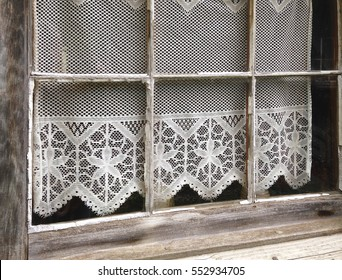A lace curtain adorns an old window in a building at the Billie Creek Village restoration in Rockville, Indiana