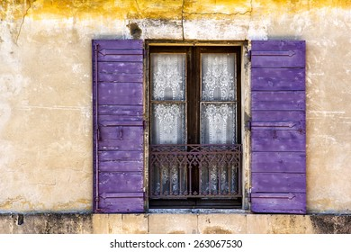 Lace Curtained Window in old wall in Arles, Provence, with violet shutters against textured ocher wall. Horizontal format.