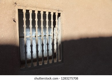 Lace curtains behind the hand-shaped traditional window bars in a window in an adobe house in New Mexico