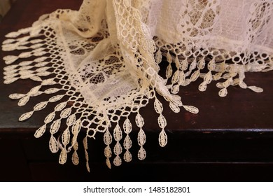 Lace fabric draped across antique wooden surface.