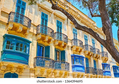 The lacelike iron balconies and bright blue wooden shutters of the old living edifice in Valletta, Malta.