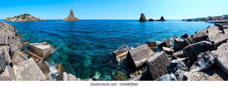 Lachea Island on Cyclopean Coast and the Islands of the Cyclops on Aci Trezza town (Italy, Sicily,10 km north of Catania). Known as Isoles Dei Ciclopi Faraglioni. People are unrecognizable.