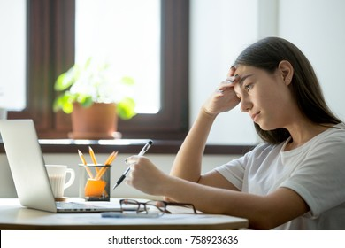 Lack of energy, boredom at work. Attractive millennial woman studying on laptop and preparing graduating from university. Tired female freelancer with headache holding pen and analyzing business task.