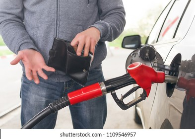 Lack of money for gasoline and fuel. Expensive gasoline. Driver man holds one dollar end empty wallet against the background of a fuel nozzle in the gas tank. increase in gasoline prices concept.