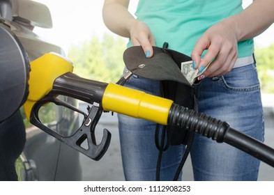 Lack of money for gasoline and fuel. Expensive gasoline. Women driver showing one dollar and empty wallet against the background of a fuel nozzle in the gas tank. Increase in gasoline prices concept.