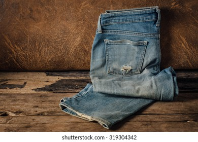 lack old jeans on wooden floor with brown leather background