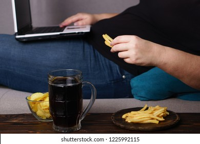 lack of physical activity, remote work, laziness, homebody. Lonely woman watching series at laptop drink beer eat junk food