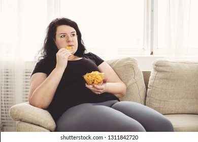 lack of physical activity, sedentariness, imbalanced nutrition, laziness, homebody. fat woman overeating junk food