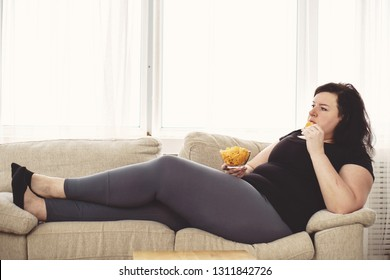 lack of physical activity,sedentariness, imbalanced nutrition, laziness, homebody. fat woman overeating junk food