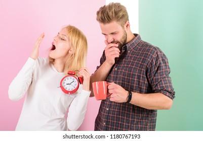 Lack of sleep. Couple sleep not enough time. Family drink morning coffee yawning faces. Hate morning awakening. Harmful habit to oversleep. Couple oversleep awakening hold alarm clock.