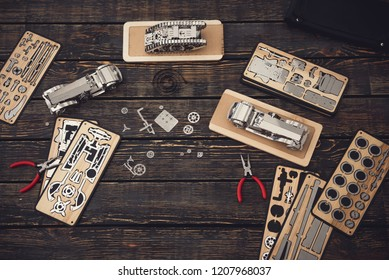 Laconic image of the table with pliers and parts of wooden constructor on it