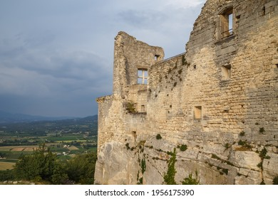 Lacoste, Provence, France. Ruined stone walls with windows of the Castle of Marquis de Sade. Provence countryside in the background.
