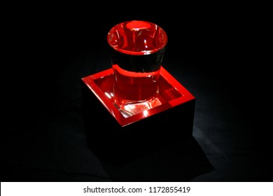Lacquered red container, masu, and glass for drinking or measuring sake on black background