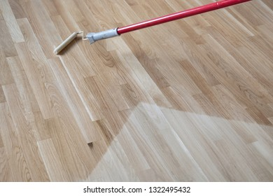 lacquering Varnishing a polished oak parquet floor by paint roller first layer.