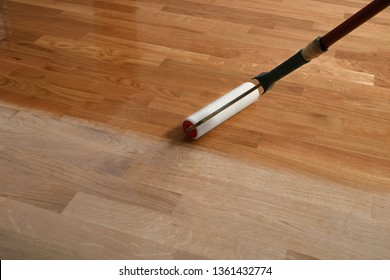 Lacquering wood floors. Worker uses a roller to coating floors. Varnishing lacquering parquet floor by paint roller - second layer. Home renovation parquet