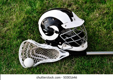 Lacrosse stick, ball and helmet on grass