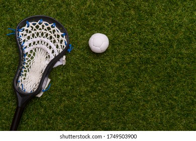 Lacrosse stick and white  ball on grass background. Team sport concept.
