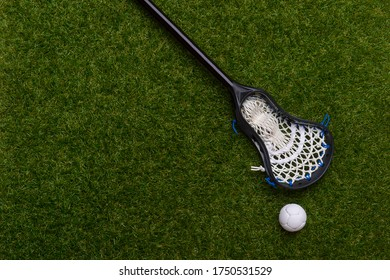 Lacrosse stick and white  ball on grass background. Lacrosse is a team sport