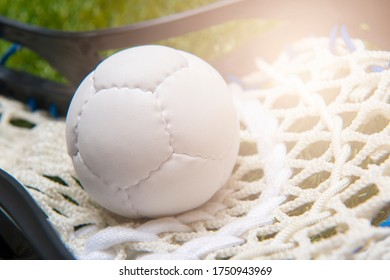 Lacrosse stick and white  ball on grass background. Lacross is a team sport