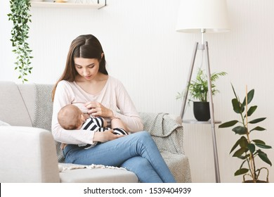 Lactation concept. Young mother breastfeeding her baby on sofa at home