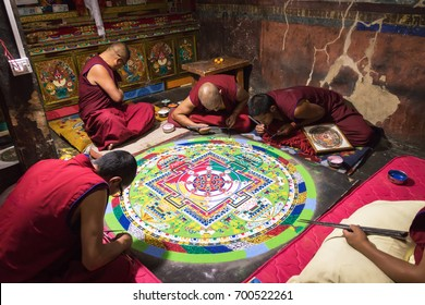 Ladakh district - INDIA - August 13, 2017: Tibetian monks constructing mandala from color sand in Thiksay monastery. Mandalas transmit positive energies to the people who view them.