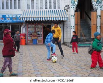 LADAKH, INDIA - April 6, 2017: local children playing football at the street of Main Bazaar, Ladakh, India