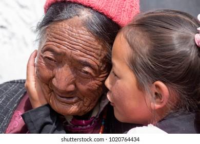 LADAKH, INDIA - JUNE 26, 2015 : Unidentified tibetan buddhist old women and child during Hemis Festival in Ladakh, North India