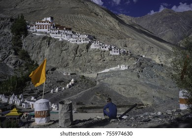 Ladakh, India, Nubra valley, Disket, a lonely watcher sits in the foreground with a tellow flag and the old Disket monastery sits on the hill in the background