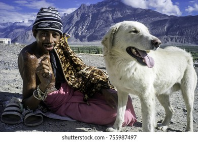 Ladakh, India, Nubra valley, Disket, July 2017, a heavily scarred beggar with a woolen cap and naked chest sits on the ground with his white Ladakhi dog standing next to him