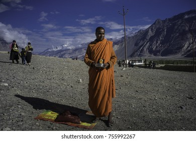 Ladakh, India, Nubra valley, Disket, July 2017, a begging monk in a saffron robe stands with his bowl while two women and a kid in the middle walk past
