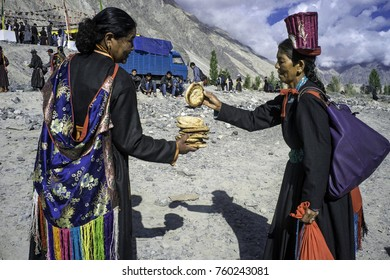 Ladakh, India, Nubra valley, July 2017, a woman in traditional Ladakhi clothes offers freshly baked bread to another woman wearing a typical Ladakhi hat