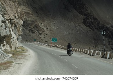 LADAKH, INDIA - SEP 13, 2017 - Motorcycle on narrow road above the Indus River, Ladakh, India