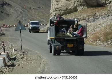 LADAKH, INDIA - SEP 13, 2017 - Workers in back of lorry on narrow road above the Indus River, Ladakh, India