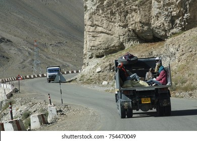 LADAKH, INDIA - SEP 13, 2017 - Workers in bsack of lorry on narrow road above the Indus River, Ladakh, India