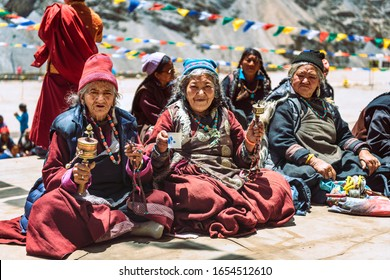 LADAKH, KASHMIR / INDIA – JUNE 22, 2019: Old women in traditional tibetan dress with buddhist prayer wheel sitting in lotus position in Ladakh, Kashmir, India.