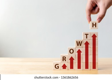 Ladder career path for business growth success process concept.Hand arranging wood block stacking as step stair with arrow up and word GROWTH