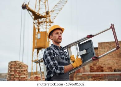 Leiter in der Hand. Bauarbeiter in Uniform- und Sicherheitsausrüstung haben eine Baustelle.