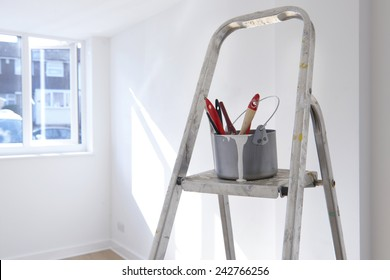 ladder with paint pot and brushes standing in empty room